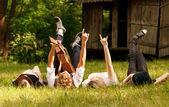 Vier freunde, die im gras liegend — Stockfoto