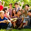 Royalty-Free Stock Photo: Happy school friends singing by guitar