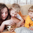 Children with beagle puppy in the bed — Stock Photo