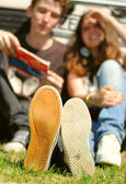Młoda para siedzi w pobliżu automatyczne zbliżenie stóp obrazu — Zdjęcie stockowe