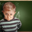 Clever pupil boy in eyeglasses near schoolboard — Stock Photo #29326359