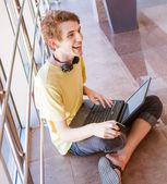 Olumlu ifade laptop ve kulaklık genç çocuk — Stok fotoğraf