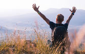 Man greeting sunrise on the mountain — Stock Photo