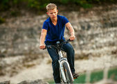 Youmg man riding a bike off road — Stock Photo