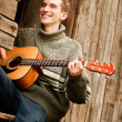 Smiling guitarist played by guitar in lost village — Stock Photo
