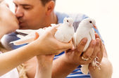 Kissing love couple with pare of white doves — Stock Photo