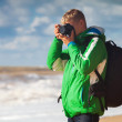 Young man with camera makes sea snapshot — Stock Photo