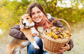 Pretty woman with her favorite pet in autumn forest — Stock Photo