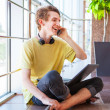 Cheerful smiling teenage boy talking by phone — Stock Photo