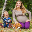 Happy smiling pregndnt woman with little son and dog on the walk — Stock Photo #36631949