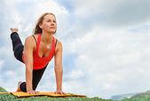 Yuong woman makes flexible yoga exercise — Стоковое фото