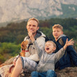 Father with sons and favorite puppy on the mountain walk — ストック写真
