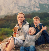 Father with sons and favorite puppy on the mountain walk — Stock Photo