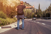 Hitchhiking traveler on the road — Stock Photo