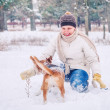 Stock Photo: Womplaying with her pet in winter park