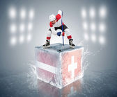 Hockey player on the cube with Latvia and Switzerland flags — Stock Photo
