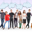 Smiling young people group with funny cartoon clouds — Stock Photo
