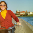 Happy woman riding by bysicle along the waterfront — Stock Photo