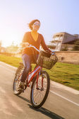 Happy young woman ride by bicycle — Stock Photo