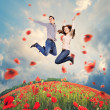 Happy young couple jumping in poppies field — Stock Photo #44139511