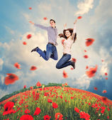 Happy young couple jumping in poppies field — Стоковое фото