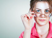Female putting on glasses — Stockfoto