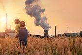 Father with son over chemical plant emissions — Stock Photo