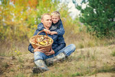 Father and son with full basket of mashrooms on the forest glade — Stock Photo