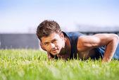 Healthy young man doing pushups — Stockfoto