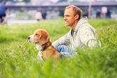 Man with his dog sitting in green grass — Stock Photo