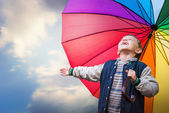 Boy with bright rainbow umbrella — Stock Photo