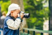 Little boy with photo camera makes a shoot — Stock Photo