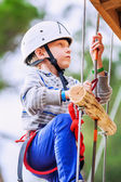 Boy climbing rope-ladder in adrenalin park — Stock Photo