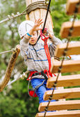 Boy climbing rope-ladder — Stock Photo
