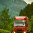 Red truck on mountain highway in the evening — Stock Photo #50800699