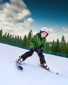 Little skier going down from snowy hill — Stok fotoğraf