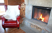 Fireplace and armchair — Stockfoto