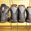 Old snowboard boots at ski rental — Stock Photo