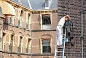 Man correcting lamp in front of building of dutch parliament - T — Stock Photo