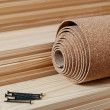 A roll of cork and some nails lie on the floor battens — Stock Photo
