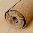A roll of cork lies on the wooden floor — Stock Photo