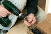 Man installs nail into the screw gun — Stock Photo