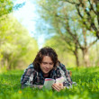 A young man reads a book in the spring garden — Stock Photo