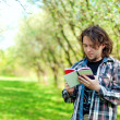 A young man reads a book in the spring garden — Stock Photo #37004211