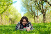 A young man reads a book in the spring garden — ストック写真