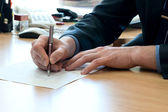 Man writes something on a white paper. Office work — Foto de Stock