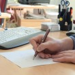Stock Photo: Mwrites something on white paper. Office work