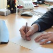 Man writes something on a white paper. Office work — Stock Photo #42021461