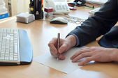 Man writes something on a white paper. Office work — Foto de Stock