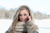 Girl using mobile smart phone in the winter park — Stock Photo